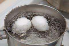 Ebullición de dos huevos Foto de archivo