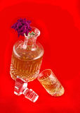 Ecanter with jigger for beverage and flower. Crystal decanter with jigger for alcoholic beverage and flower over red background Royalty Free Stock Photos