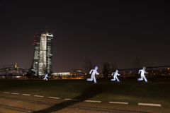 The ECB EZB in Frankfurt am Main at night with refugees. Frankfurt, Germany - 03-13-2016: The new ECB in Frankfurt at night during the luminale 2016 with an Royalty Free Stock Image