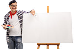 Eccentric artist posing next to a canvas Stock Images