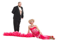 Eccentric Fat Man in a Tuxedo and Beautiful Lady in an Evening D. Ress Lying on Floor, drag queen artists on white background stock photography