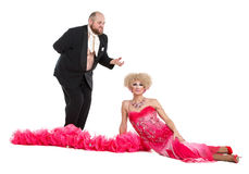 Eccentric Fat Man in a Tuxedo and Beautiful Lady in an Evening D. Ress Lying on Floor, drag queen artists on white background royalty free stock photography