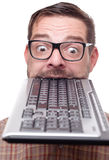 Eccentric geek biting into a keyboard Stock Photo