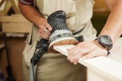 Eccentric grinding machine makes wooden polishing of bar plank Royalty Free Stock Photo