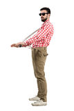 Eccentric hipster stretching suspenders looking at distance Royalty Free Stock Photography