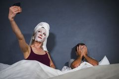 Eccentric housewife with makeup facial mask and towel taking selfie in bed and husband with desperate face expression in weird man. Funny lifestyle portrait of stock photo