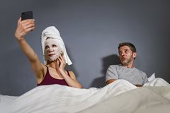 Eccentric housewife with makeup facial mask and towel taking selfie in bed and husband with desperate face expression in weird man stock photography