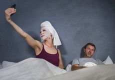 Eccentric housewife with makeup facial mask and towel taking selfie in bed and husband with desperate face expression in weird man royalty free stock photos