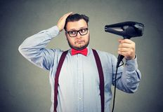 Eccentric man in glasses drying his hair. Fashionable eccentric man in glasses drying his hair on gray wall background stock photography