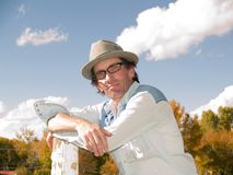 Eccentric man leaning to a fence post. Eccentric man wearing a fedora and a western shirt leaning to a fence post Stock Image