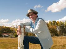 Eccentric man leaning to a fence post. Eccentric man wearing a fedora and a western shirt leaning to a fence post Royalty Free Stock Image