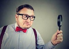 Curious young man using magnifier royalty free stock photos