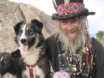 Eccentric older gentleman with his dog. Eccentric older gentleman with a top hat and dreadlocks sitting by his dog Royalty Free Stock Image
