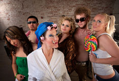 Eccentric woman hanging out with party kids Stock Images