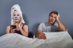 Eccentrico e casalinga strana con la maschera facciale di trucco ed asciugamano facendo uso del telefono cellulare a letto e del  fotografia stock libera da diritti