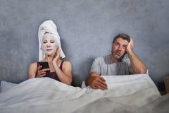 Eccentrico e casalinga strana con la maschera facciale di trucco ed asciugamano facendo uso del telefono cellulare a letto e del  immagini stock