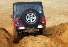 Eccitando fuori dal drivig della strada in un pozzo di conquista della sabbia Immagini Stock