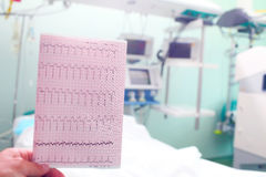 ECG in doctors hand on the background of medical ward. ECG in doctors hand on the background of hospital room royalty free stock photos