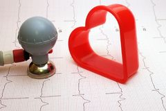 ECG electrode and heart shaped gingerbread cutter. ECG electrode and heart shaped red plastic gingerbread cutter with ECG record as background stock images
