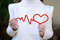 ECG et lignes de coeur du fil rouge dans les mains de Image libre de droits