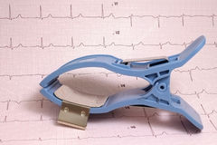 ECG limb electrode on ECG paper with record. ECG limb clamp electrode on ECG paper with record of ECG curves royalty free stock photo