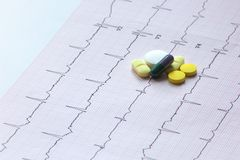 ECG medication in pill form and capsules. Pills grouped on a ECG sheet Royalty Free Stock Photography