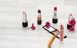 Echado, imagen de cosméticos Vista superior de la tabla del maquillaje del ` s de las mujeres incluyendo los lápices labiales, lo fotos de archivo libres de regalías