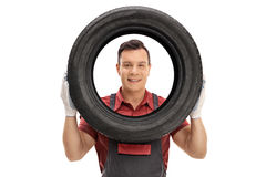 Мechanic looking at the camera through a tire Royalty Free Stock Photography