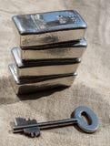 Eche las barras de plata y la llave a la caja fuerte contra una textura áspera de la tela fotografía de archivo libre de regalías