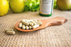 Echinacea: The Herbal Immune Booster capsules. Pills immunomodul. Ator. Echinacea tablets in a wooden spoon on a background of bottle of tablets, green fruits Royalty Free Stock Photography
