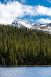 Echo Lake Mount Evans Colorado - Snow Cap Mountain. Snow covered Mount Evans locaed near Denver Colorado - Snow Capped Mountains and green pine forest - nature stock photo