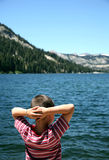 Echo Lake watcher. Boy relaxing and looking out over Echo Lake in California stock photo