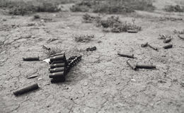 Echo of war. Bullet cases on the desert ground Stock Image