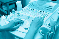 Echography specialist hands at work, blue toning Royalty Free Stock Images