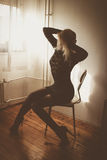 Echoing thoughts. Blond woman in mini black dress sitting by the window royalty free stock photo