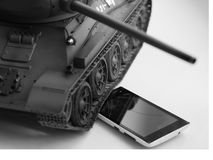 Echt stuk speelgoed versus virtueel Stuk speelgoed tank versus Slimme telefoon Stock Fotografie