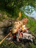 Echte Duitse die Stockbrot over een kampvuur wordt gemaakt stock afbeelding