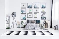 Echte foto van een bed die zich tussen een lamp en een stoel in een bri bevinden royalty-vrije stock afbeelding