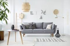Echte foto van een eenvoudig woonkamerbinnenland met kussens op gra stock foto