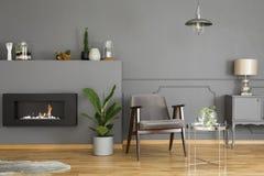 Echte foto van een grijze leunstoel die zich in een moderne, eenvoudige livin bevinden stock afbeeldingen