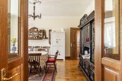 Echte foto van een ruim, houten eetkamerbinnenland met een reeks royalty-vrije stock afbeeldingen