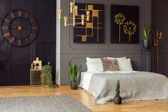 Echte foto van een ruim slaapkamerbinnenland met grijze muren, klok, schilderijen, installaties, bed en gouden accenten stock foto's