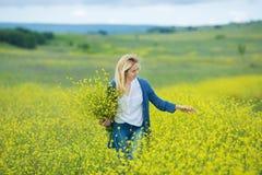 Echte leuke damevrouw die in weide van gele bloemen bloemboeket snuiven Aantrekkelijk mooi jong meisje die van de warme som genie stock afbeelding