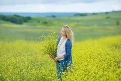 Echte nette Damenfrau in der Wiese von gelben Blumen Blumenblumenstrauß schnüffelnd Attraktives schönes junges Mädchen, welches d Lizenzfreies Stockfoto