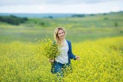 Echte nette Damenfrau in der Wiese von gelben Blumen Blumenblumenstrauß schnüffelnd Attraktives schönes junges Mädchen, welches d Stockfotos