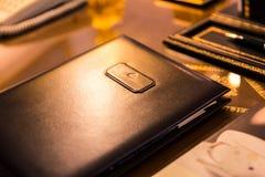 Echter Brown-Leder-Ordner auf glänzender Schreibtisch-Oberfläche stockfotografie