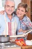 Echtgenoot die een kookboek bekijkt Stock Foto