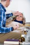 Echtgenoot die jonge vrouw met verwarmingspijp thuis behandelen stock foto