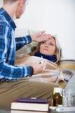 Echtgenoot die jonge vrouw met verwarmingspijp thuis behandelen royalty-vrije stock foto