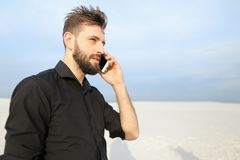 Echtgenoot die op smartphone met vrouw het lopen bij kust spreken sm Stock Fotografie